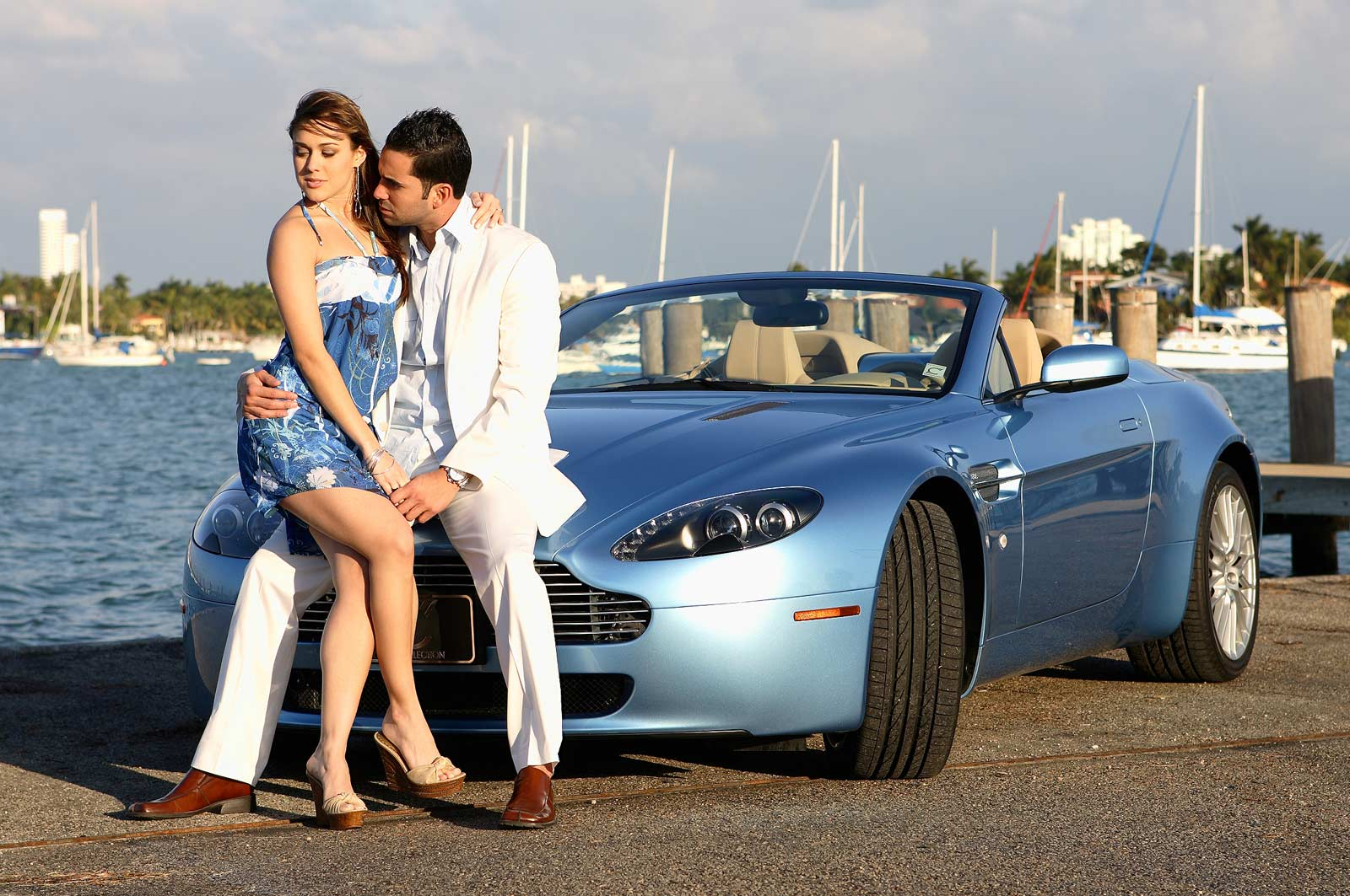 Couple Engaged in front of blue sport car
