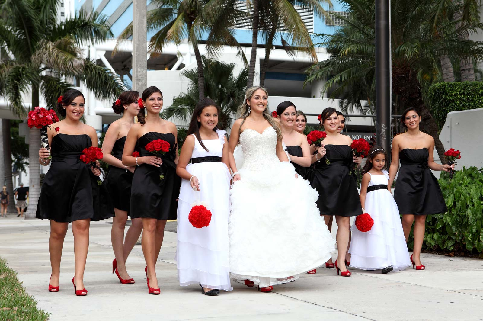 Bridesmaids in Black Dress with Flower Girls walking with beautiful bride