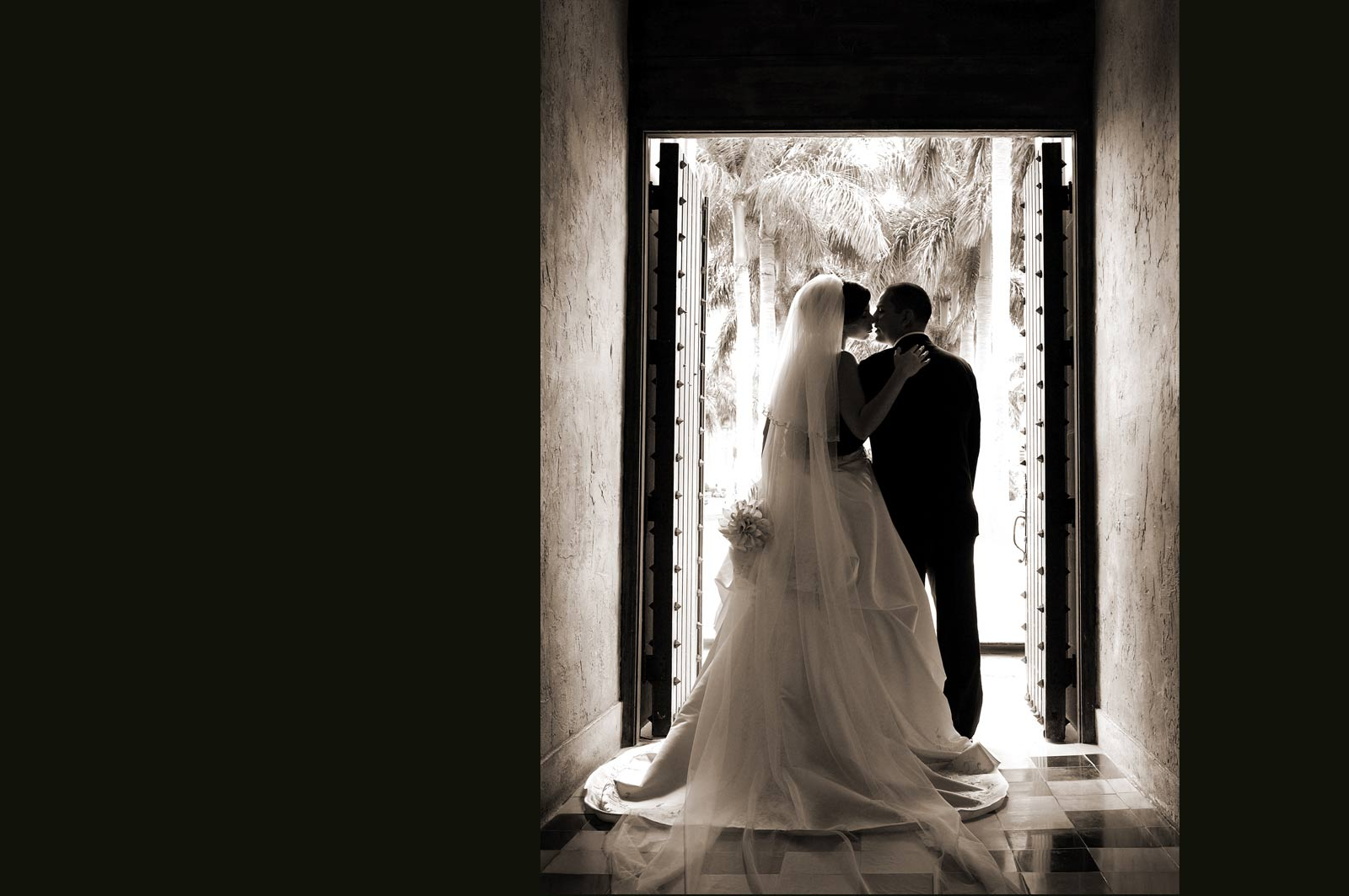 Romantic Wedding Couple Kissing under Door Frame in Sepia